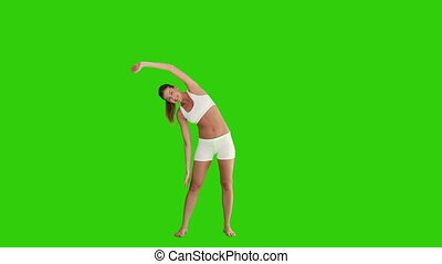 Dark haired female doing relaxation exercise against a green...