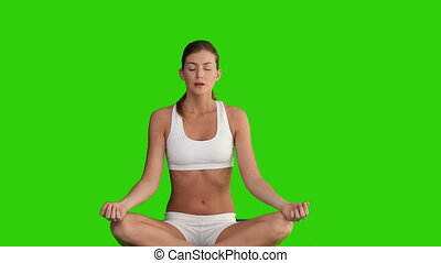 Dark haired female doing yoga against a green screen