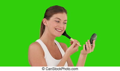 Dark haired female putting on make-up