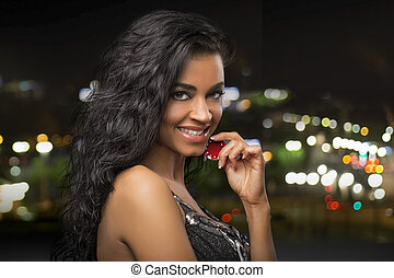 dark-haired girl at city background with casino chips