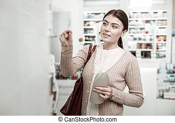 Dark-haired green-eyed woman choosing care cosmetics in pharmacy store