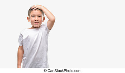 Dark haired little child stressed with hand on head, shocked with shame and surprise face, angry and frustrated. Fear and upset for mistake.