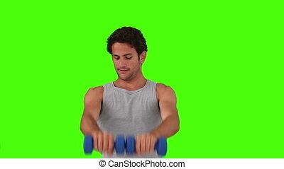 Dark-haired man doing bodybuilding exercises