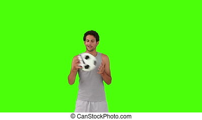 Dark-haired man in sportswear playing with a soccer ball