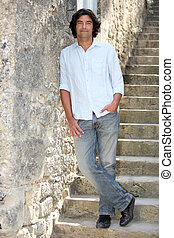 Dark haired man leaning against stone wall