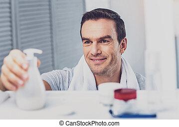 Dark-haired man putting liquid soap on shelf