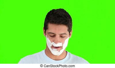 Dark-haired man shaving