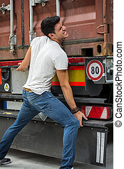 Dark-haired man trying to lift heavy vehicle
