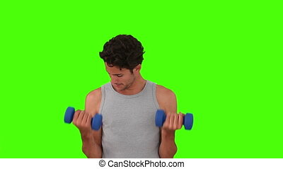 Dark-haired man using dumbbells