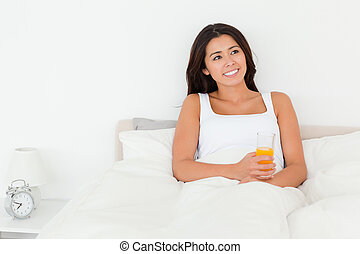 dark-haired woman holding orange juice sitting in bed looking at the ceiling in bedroom
