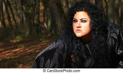 Dark Haired Woman In Black Staring Into The Distance In Autumn Forest