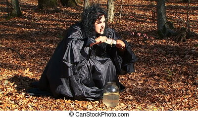 Dark Haired Woman In Black Tearing Dried Fish In Autumn Forest