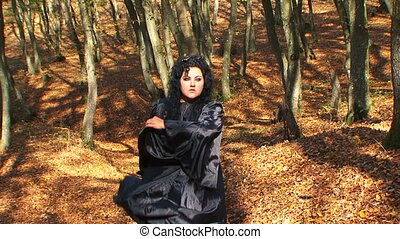 Dark Haired Woman In Black Walking In Autumn Forest