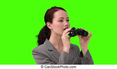 Dark-haired woman in suit using a pair of binoculars
