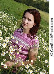 dark-haired woman in wild chamomile