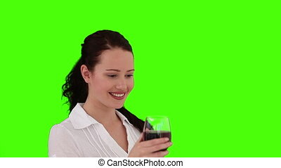 Dark-haired woman is enjoying a glass of red wine