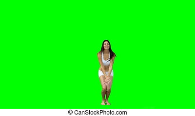 Dark haired woman jumping into the shape of an x