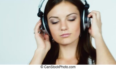Dark-haired woman listening to music on headphones and...