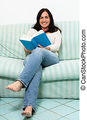 Dark haired woman lying on couch and reading a book
