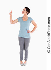 Dark-haired woman pointing at copy space