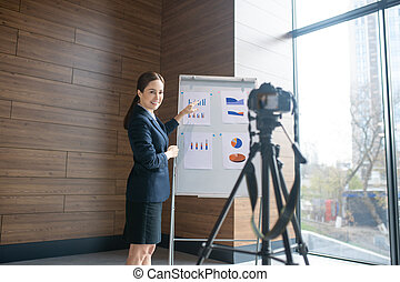 Dark-haired woman smiling while filming business blog for her followers