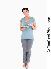 Dark-haired woman using a tablet computer against a white...