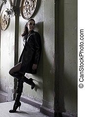 dark model wearing a leather coat and boots in an old...