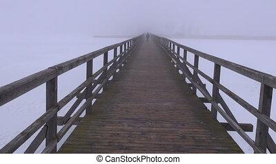dark morning fog on wooden bridge