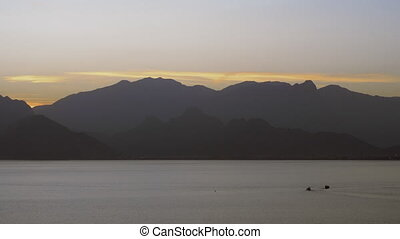 Dark mountains by the sea in the evening