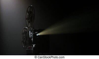 Dark movie theater. Projector illuminated by lights...