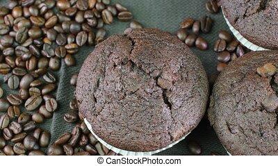 Dark muffins and coffee beans on black background. - Dark...