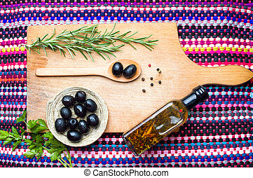 Dark olives with spices on a wooden board