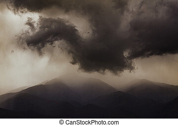 Dark ominous clouds. Dramatic sky. Dragon silhouette.