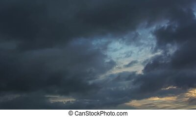 Dark, ominous storm clouds appear to struggle against the sky as they billow and drift in the wind, in timelapse