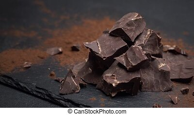 Dark or milk organic chocolate pieces on dark concrete ...