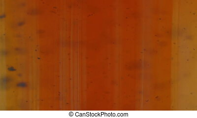 abstract background with dark particles flowing inside of orange fluid