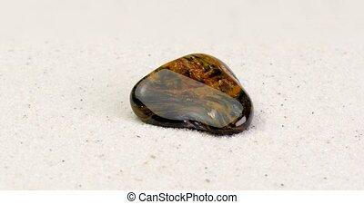 Dark pietersite gemstone rotating on white sand - Dark...