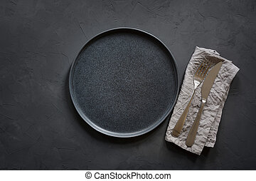 Dark place setting on black table. Top view.