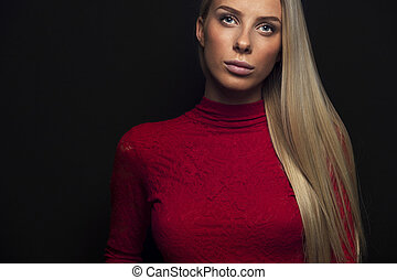 Dark portrait of a blonde woman in red dress