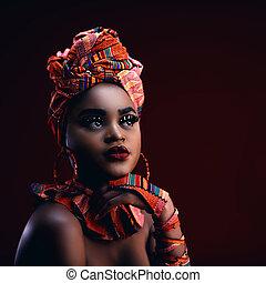 dark portrait of beautiful african woman in traditional nigerian costume