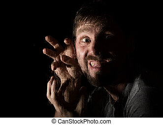Dark portrait of scary bearded man with smirk, expresses different emotions. Drops of water on a glass, hand and male face