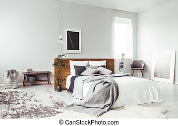 Dark poster in bright bedroom