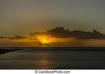 Dark rain cloud and rain at sunrise over the Atlantic Ocean