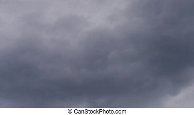 Dark rain clouds move across the screen from left to right