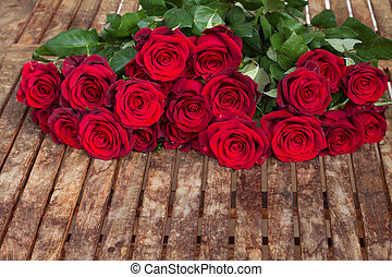 dark red roses on table - dark red roses laying on wooden...