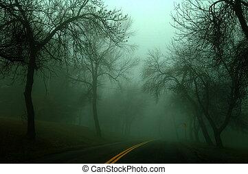 low key image of a dark misty road