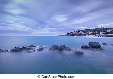 Dark Rocks in a blue ocean on twilight. Castiglioncello, Italy