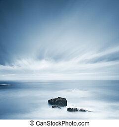 Dark rocks in a blue ocean under cloudy sky in a bad weather...