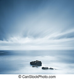 Dark rocks in a blue ocean under cloudy sky in a bad...
