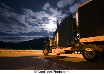 Dark semi truck reefer in night light with moony clouds -...